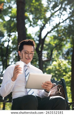 Asian businessman with coffee and digital tablet sitting on the bench
