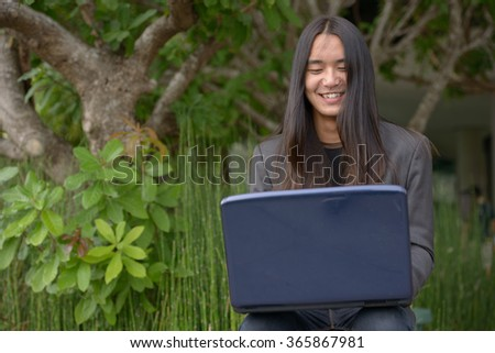 Asian businessman with long hairstyle outdoors smiling and using laptop computer