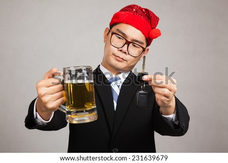 Asian businessman with party hat decide drink or drive with beer and car key on gray background - stock photo
