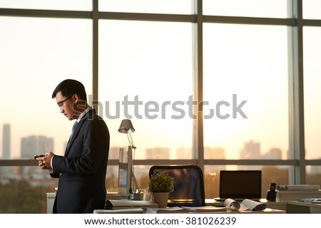 Asian businessman with smartphone is going to work in office after sunset - stock photo