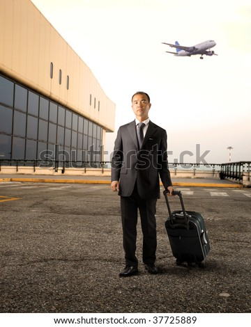 asian businessman with trolley at the airport - stock photo