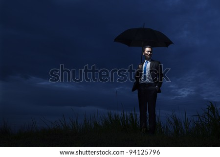 Asian businessman with umbrella standing on a cloudy day - stock photo