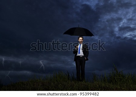 Asian businessman with umbrella standing on a cloudy day with thunderstorm