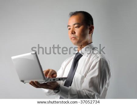 asian businessman working on mini pc - stock photo