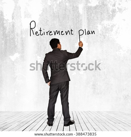 Asian businessman writing Retirement plan text on wall background - stock photo