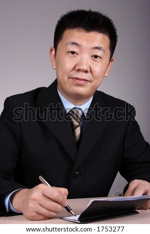 Asian businessman writting a cheque. - stock photo