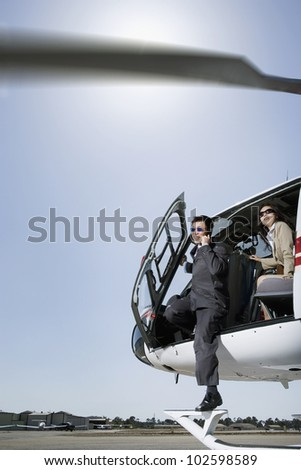 Asian businesspeople getting out of helicopter - stock photo