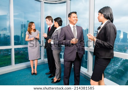 Asian Businesspeople standing and talking in front of office window - stock photo