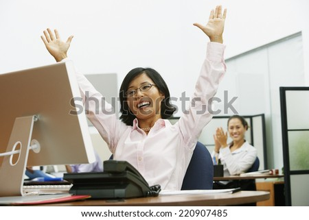 Asian businesswoman cheering at desk - stock photo