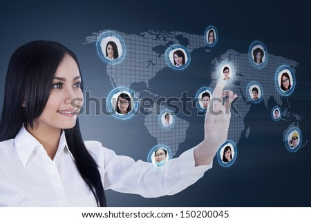 Asian businesswoman clicking on social networking map - stock photo
