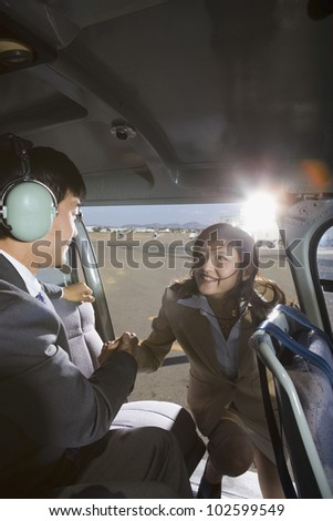 Asian businesswoman getting into helicopter - stock photo