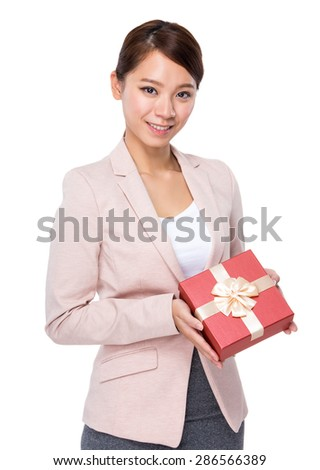 Asian businesswoman holding a giftbox to client - stock photo