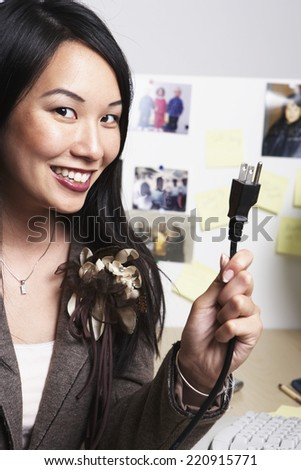 Asian businesswoman holding up plug - stock photo