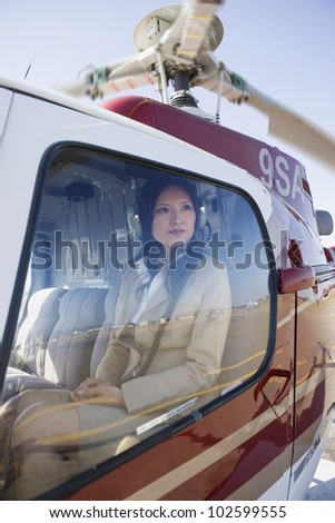 Asian businesswoman in helicopter - stock photo