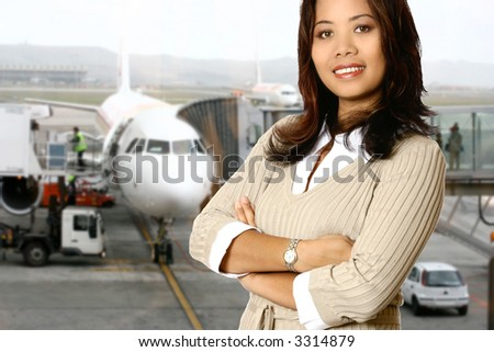 Asian businesswoman in the departure hall about to go on her business trip, passenger boarding  plane in the background. - stock photo