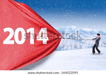 Asian businesswoman is pulling big number of 2014 on snow mountain - stock photo
