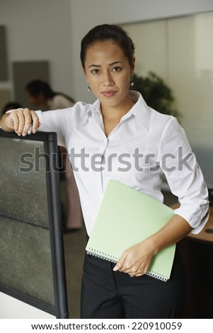 Asian businesswoman leaning on cubicle wall - stock photo