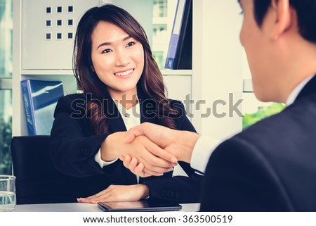 Asian businesswoman making handshake with a businessman in the office - stock photo