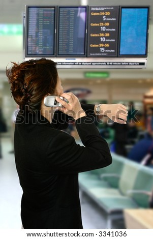 Asian businesswoman on her cellphone while looking at her watch, in the arrival/departure hall of the airport. Concept of time pressure and business air travel.