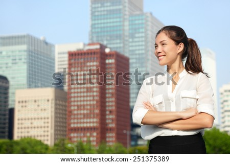 Asian businesswoman portrait in Tokyo. Happy confident young smart professional in casual business outfit in Japanese downtown Tokyo with skyline in the background. - stock photo