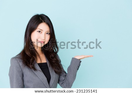 asian businesswoman showing isolated on blue background