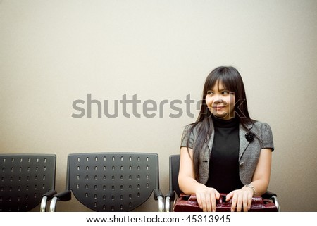 asian businesswoman sitting alone in the waiting room for an appointment - stock photo
