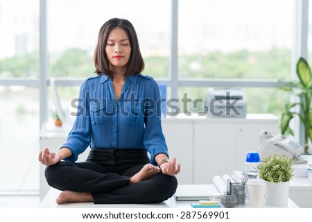 Asian businesswoman sitting on table and meditating - stock photo