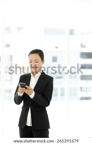 Asian Businesswoman texting on smart phone - stock photo
