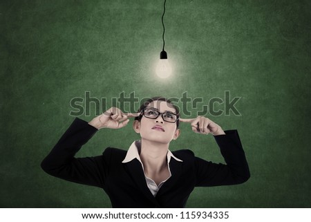 Asian businesswoman thinking with a light bulb. Shot over a chalkboard - stock photo
