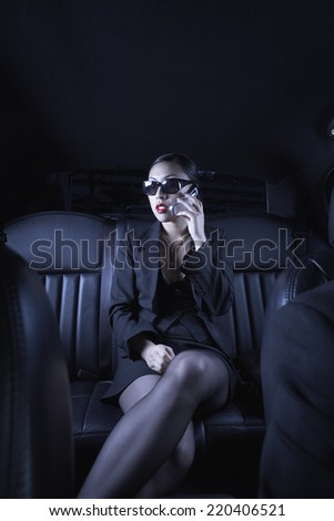 Asian businesswoman using cell phone in back seat of car - stock photo