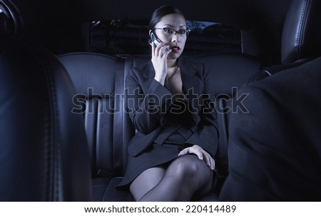 Asian businesswoman using cell phone in back seat of car