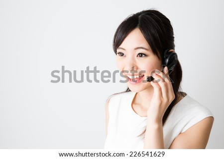 asian businesswoman using headset on white background - stock photo