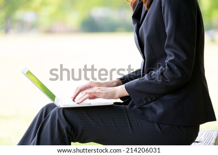 asian businesswoman using laptop computer in the park