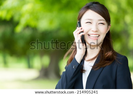 asian businesswoman using smart phone in the park - stock photo