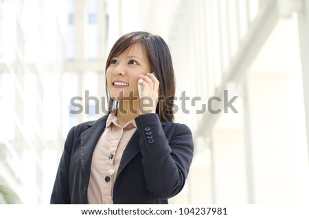 Asian Businesswoman walking on street passing by an office building. - stock photo