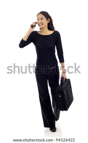 Asian businesswoman walking while talking on mobile phone isolated over white background