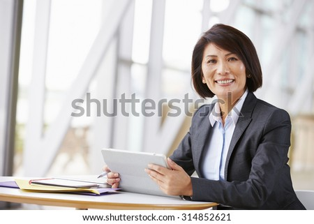 Asian businesswoman with digital tablet,  smiling to camera - stock photo