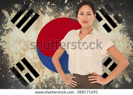 Asian businesswoman with hands on hips against korea republic flag in grunge effect - stock photo