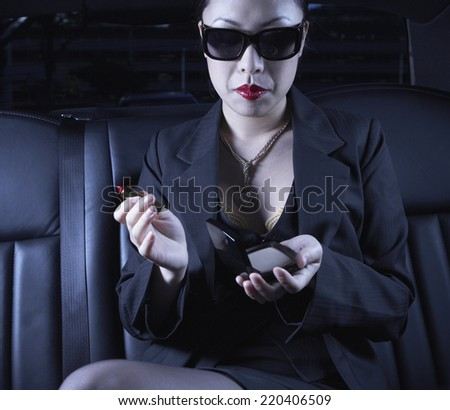 Asian businesswoman with make up in back seat of car - stock photo