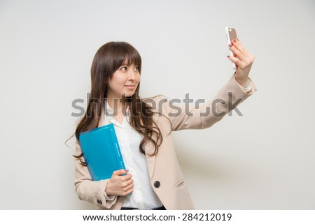 Asian businesswoman with smartphone and documents
