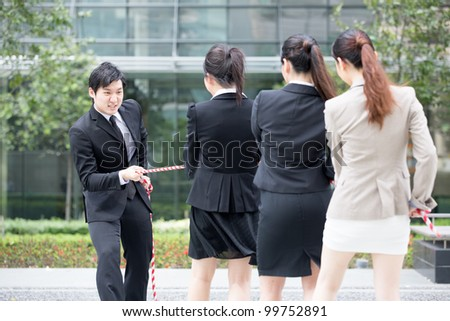 Asian businesswomen playing tug of war against one businessman.