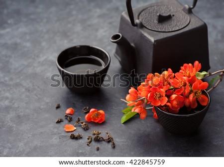 Asian cast iron tea set with green tea. Green tea and flowers, black background - stock photo
