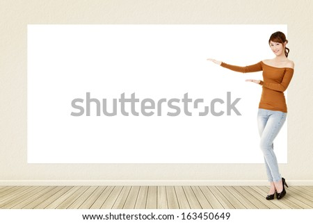 Asian casual smiling woman standing and showing blank white banner, board, placard or poster. Copy-space for advertise. - stock photo