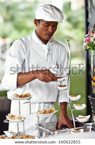Asian chef laying a table with luxury food and drinks on wedding. - stock photo