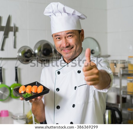 Asian chef sgowing plate with sushi and OK. Focus on sushi.  - stock photo