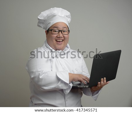Asian chef with laptop computer in her hands on plain background