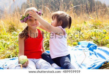 Asian child along with his caucasian girlfriend on a picnic in the mountains on a Sunny day. Girl wears a headband of flowers on the head her friend