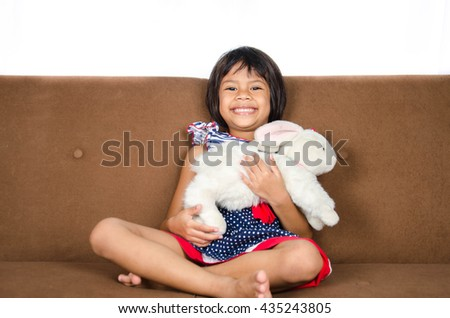 Asian Child And Doll Relax on Sofa