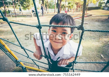 Asian child climbing in a rope at adventure park. Handsome boy smiling happily and having fun at children playground. Outdoors with bright sunlight on summer day. Vintage film filter effect.