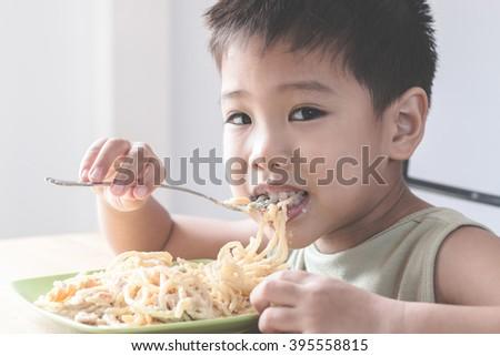 Asian child eating spaghetti - stock photo